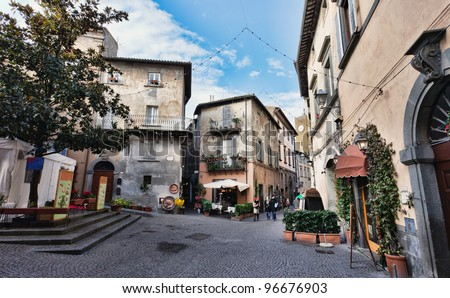 Orvieto, Umbria, Italy, narrow street with small shops. Orvieto is a city in southwestern Umbria, Italy situated on the flat summit of a large butte of volcanic tuff. - stock photo
