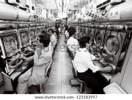 OSAKA - AUG 20:Japanese men plays in Pachinko parlor on August 20 2006 in Osaka, Japan.The Japanese government estimates the annual revenues of the Pachinko industry is 29 trillion (US$378 billion) - stock photo