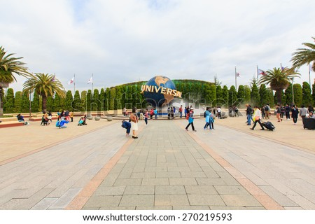 Osaka, Japan - Apr 9: View of tourists and Universal Globe outside the Universal Studios Theme Park in Osaka, Japan on Apr 9, 2015. The theme park has many attractions based on the film industry. - stock photo