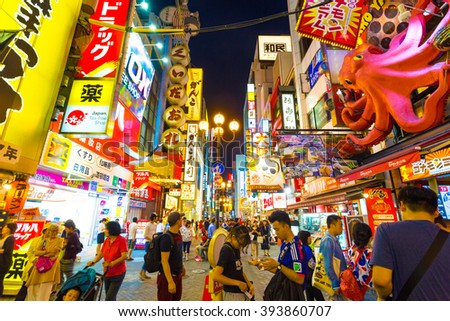 OSAKA, JAPAN - JUNE 23, 2015: Tourists around pedestrian walking street at Dotonbori arcade under the iconic oversized octopus and night light signs in Namba district - stock photo