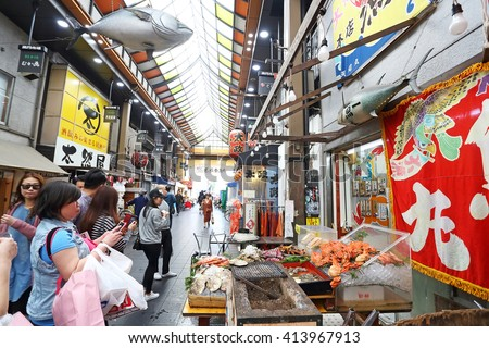 OSAKA, JAPAN - NOV 6: Tourists shopping and visit seafood prices in shop in shop  in Kuromon Ichiba market on November 6, 2015 in Osaka, Japan. it is market places popular in Osaka - stock photo