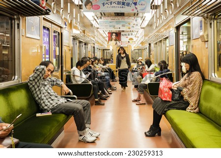 OSAKA, JAPAN, NOVEMBER 15, 2011: People are sitting after work inside a modern and clean train of the Japanese subway in Osaka, Japan. - stock photo