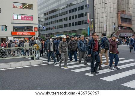Osaka, Japan - November 29, 2015:Unidentified People walk across the street at Umeda station in Osaka. It is a city in the Kansai region of Japan's main island of Honshu, - stock photo