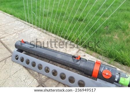 Oscillating sprinkler watering fresh green lawn grass in the autumn garden - stock photo