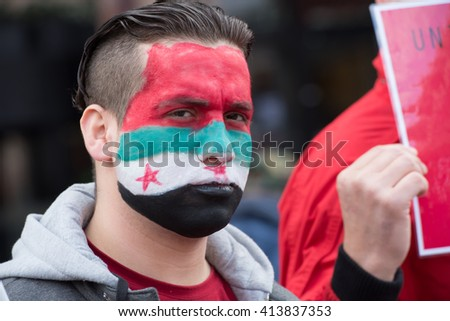 OSLO - MAY 1: A refugee with Syrian flag face paint protests during the May Day parade in Oslo, Norway, May 1, 2016. - stock photo