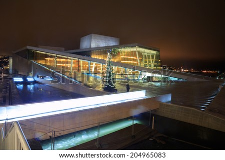 OSLO, NORWAY - DEC 31: National Oslo Opera House shines at sunrise on December 31, 2012. Oslo Opera House was opened on April 12, 2008 in Oslo, Norway - stock photo