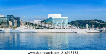 OSLO, NORWAY - SEPTEMBER 10: View from the fjord to the National Oslo Opera House and Oslo downtime against blue sky on September 10, 2014 - stock photo