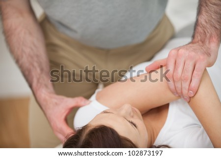 Osteopath making a joint mobilization in his medical office - stock photo