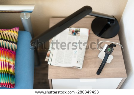 OSTFILDERN, GERMANY - MAY 21, 2015: An Apple Watch is being loaded on the bedside table using a stylish stand by manufacturer Spigen next to a magazine. The Apple smartwatch should be charged every - stock photo