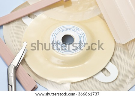 Ostomy supplies with scissors on blue background. - stock photo