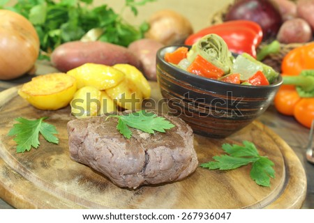 Ostrich steak with crispy baked potatoes and vegetables on a wooden board - stock photo