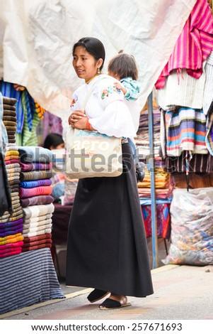 OTAVALO, ECUADOR - JAN 3, 2015: Unidentified Ecuadorian woman carries her little baby at the Otavalo Market. 71,9% of Ecuadorian people belong to the Mestizo ethnic group - stock photo