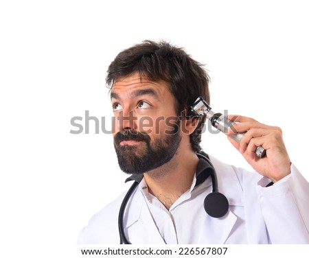 Otorhinolaryngologist with his otoscope over white background - stock photo