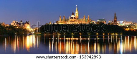 Ottawa at night over river with historical architecture. - stock photo