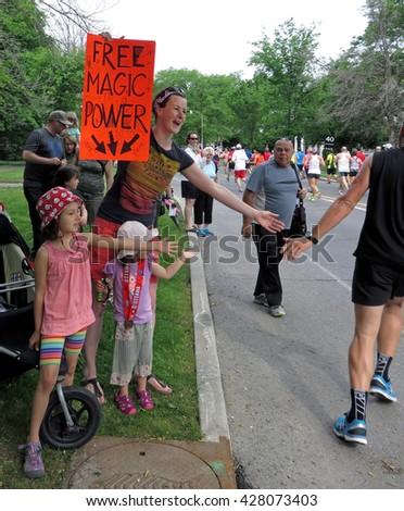 "OTTAWA, CANADA - MAY 29, 2016: An Ottawa family offers ""Free Magic Power"" to runners in the Scotiabank Ottawa Half-Marathon.                                - stock photo"