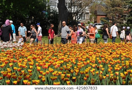 Ottawa, Canada - May 23, 2016: Tourists of different ages, sex and nationalities attending Tulips Festival in Dow's Lake. - stock photo