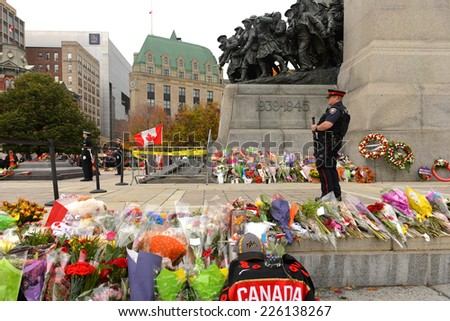 OTTAWA - OCT 25, 2014: An unidentified armed guard on duty along with the 2 ceremonial guards as mourners pay respect at the Ottawa Cenotaph the site where guard Nathan Cirillo was shot 3 days before. - stock photo