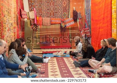 OUARZAZATE, MOROCCO - 25 NOV: Tourists watching moroccan woman weaving traditional carpet. November 25, 2008 in Ouarzazate, Morocco, Africa - stock photo