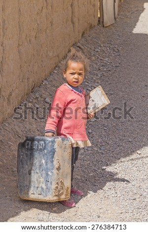 OUIRHLANE, MOROCCO, APRIL 12, 2015: Little local girl carries a canister - stock photo