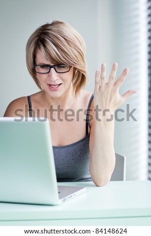 oung businesswoman showing annoyance over a problem while working on her laptop (color toned image) - stock photo