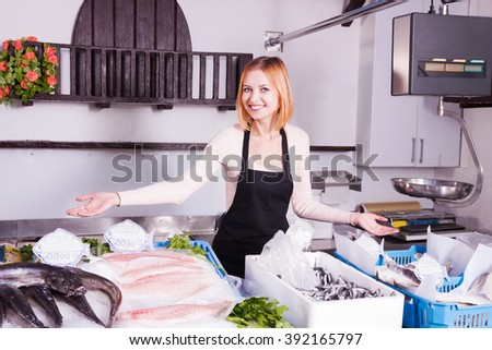 oung saleswoman offers fresh fish in a sho - stock photo