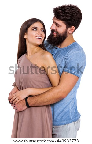 Our love will last a lifetime... Beautiful young smiling couple looking at each other and smiling while man hugging his girlfriend over white background. - stock photo