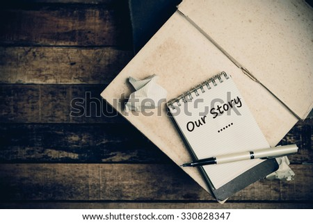 Our Story word on pages sketch book on wood table vertical  - stock photo