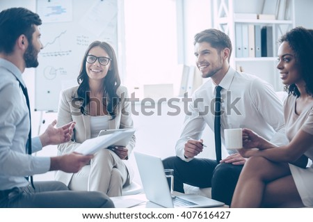 Our work is amazing! Young handsome man holding documents and discussing something with his coworkers with smile while sitting on the couch at office  - stock photo