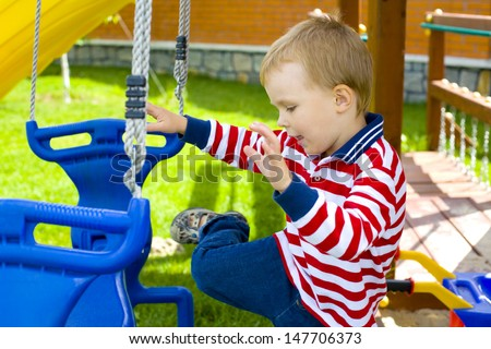 our-year-old kid on a swing - stock photo