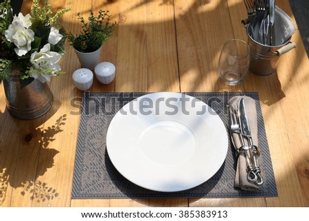 Out door table setting. Top view of porcelain plate, fork and knife hold in napkin ring with napkin on a plate mat. Pepper and salt shakers, cutlery zinc holder on the scene. Set on morning sunlight. - stock photo