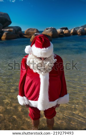 Out of context shot fo father Christmas at the ebach with his feet in the water relaxing - stock photo
