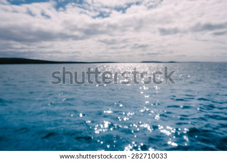 out of focus blurry image of ocean with sparkling sunlight - stock photo