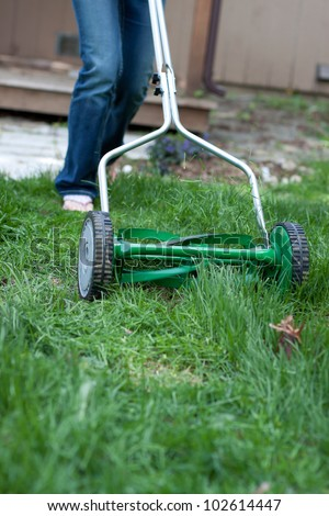 out of focus female shoes pushing a mower cutting grass in the back yard - stock photo