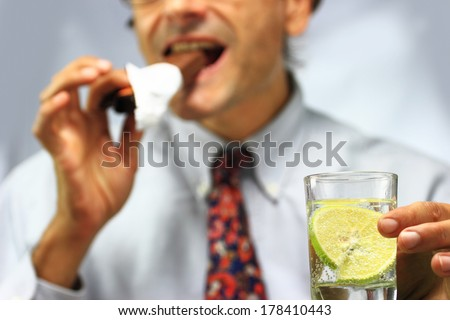 out of focus man with glass of water eating a chocolate bar - stock photo