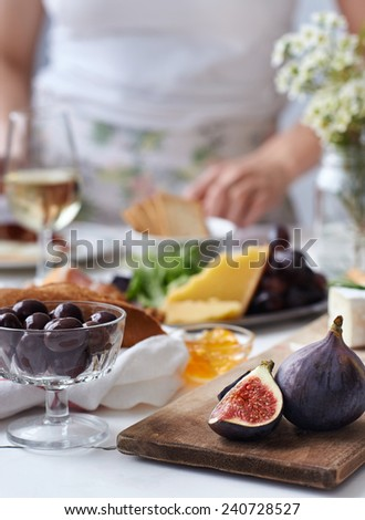 Out of focus person in background at a party with cheese and fruit snacks on the table, focus on fresh fig in foreground - stock photo