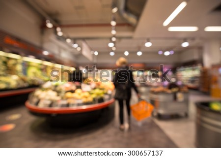 Out of focus shot of a woman shopping in a supermarket, looking at the fruit display - stock photo