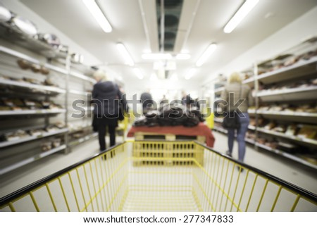 Out of focus shot of people shopping in a grocery store setting, shot from the shopping cart, great as a background in designs - stock photo