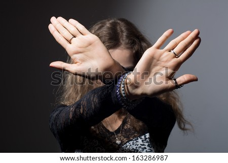 Out of focus woman with her hands signaling to stop isolated on a black background - stock photo