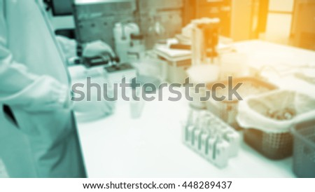 Out of focus young researcher works in chemistry laboratory as background. - stock photo