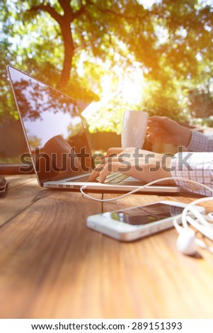 Out of office work concept vertical. Man sitting at vintage natural rough wood desk working on laptop computer drinking coffee at cafe terrace surrounded green park with color sunbeams back light - stock photo