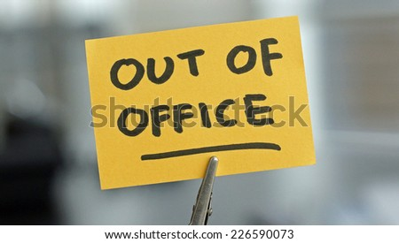Out of office written on a card at the desk - stock photo