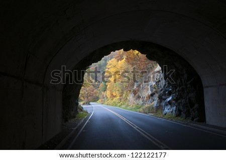 Out of the tunnel and into fall foliage. - stock photo
