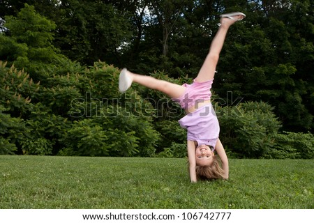 Outdoor action shot of a little girl in pink doing a cartwheel with motion in her legs - stock photo