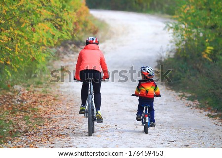 Outdoor activity with mother and child riding bikes together in autumn - stock photo