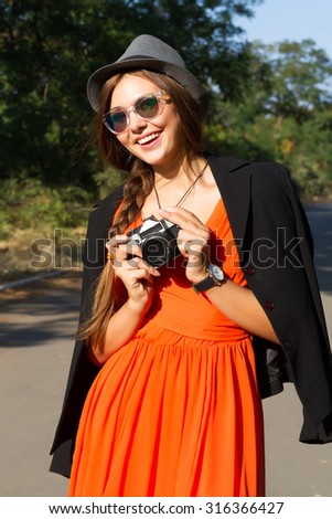 Outdoor autumn fashion portrait of young pretty stylish brunette woman posing at park,wearing trendy orange chiffon dress,black jacket,hat and sunglasses.Making photo and holding vintage camera. - stock photo