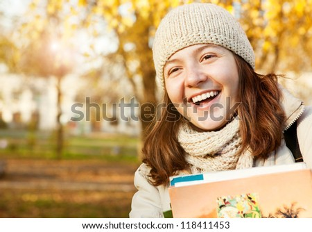 Outdoor autumn portrait happy smiling teenage girl with copybooks - stock photo