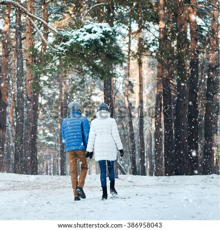 Outdoor back view portrait of cheerful  man and pretty girl enjoying the snowfall in winter forest. Young couple in love walking in wood. Christmas holidays, New Year, Valentine's day. - stock photo
