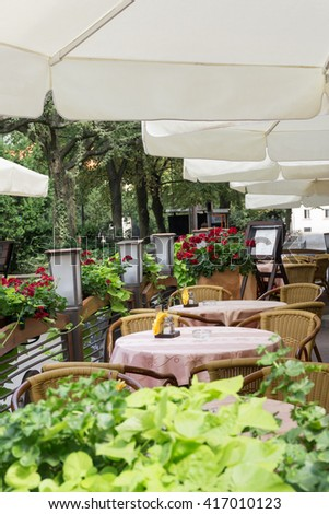 Outdoor cafe or restaurant in town. Tables covered with pink tablecloths, chairs, white umbrellas. Nobody - stock photo