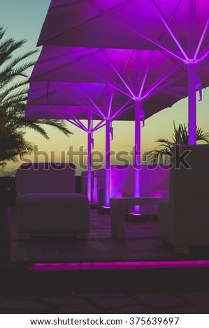 Outdoor cafe terrace illuminated with neon lights - stock photo