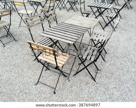 Outdoor cafe with wooden tables and chairs. - stock photo